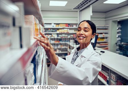 Smiling Young Female Pharmacist Wearing Labcoat Standing Behind Counter Looking For Medicine In Shel