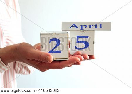 Calendar For April 25 : Women's Hands Hold Cubes With The Number 25, The Name Of The Month Of April