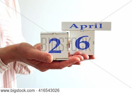 Calendar For April 26 : Women's Hands Hold Cubes With The Number 26, The Name Of The Month Of April