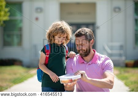 Parent And Pupil Of Primary School Schoolboy With Backpack. Schoolboy And Parent In Shirt Holding Lu
