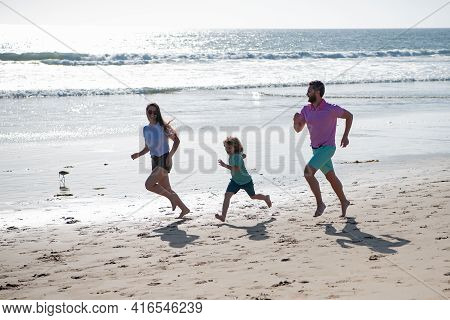 Cheerful Family Running On The Beach. Happy Mother Father With Child Son, Having Fun During Summer H