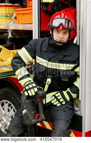 A Man Of Strong Physique In Uniform And Helmet Stands By A Rescue Vehicle.