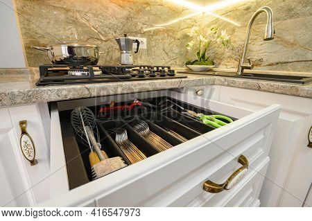 Drawers with kitchen utensils and silverware pulled out at modern classic white kitchen furniture, low angle shot