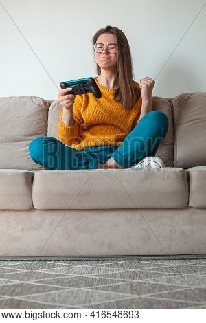 Woman Gamer Playing Mobile Phone Online Game, Is Loser, Holding In Hands Sitting On The Sofa