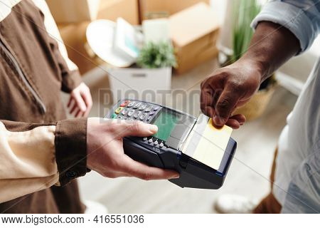 Hand of young man in workwear holding payment terminal while African male paying for loading and delivering service by credit card