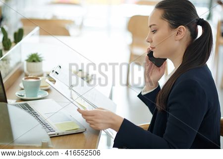 Serious Young Business Lady Reading Document And Talking On Phone With Colleague