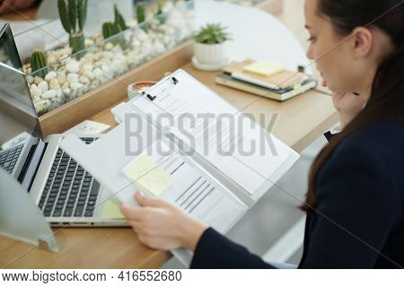 Young Businesswoman Reading Marketing Research Document And Making Phone Call To Head Of Department