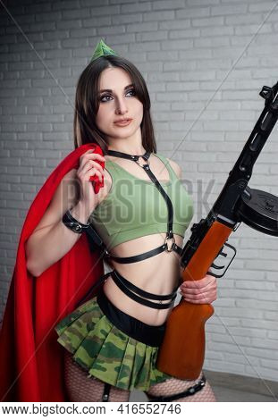 A Woman With A Red Flag In A Military Uniform With A Ppsh-41 Submachine Gun, In A Short Skirt And Le