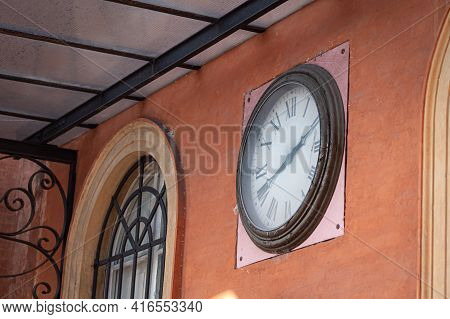 Antique Clock With Roman Numerals Placed On The Wall Of The Local Public Transport Bus Headquarters,