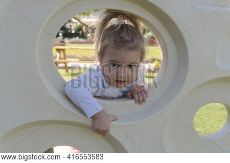 Child Climbing At Playground, Cute Caucasian Baby Girl Playing At Active Games, Outdoor Activity For