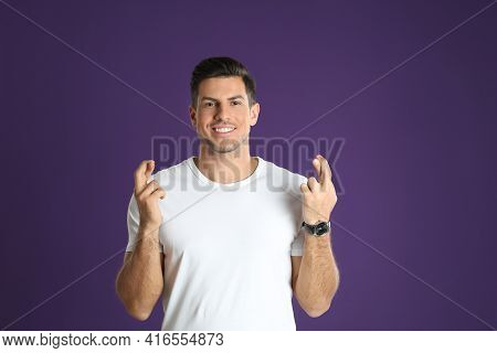 Man With Crossed Fingers On Purple Background. Superstition Concept