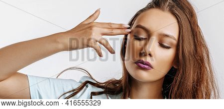 A Young Beautiful Girl Makes An Imitation Of A Gun From Her Fingers. Fashion Woman With Purple Lips