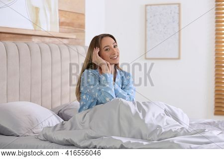 Young Woman Sitting On Comfortable Bed With Silky Linens