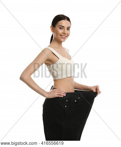 Happy Young Woman Wearing Big Jeans After Weight Loss On White Background