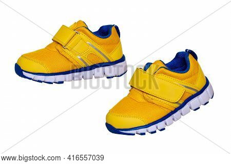 Child Shoe Fashion. Close-up Of A Pair Of Yellow Blue Child Sneaker Or Sport Shoes Isolated On A Whi