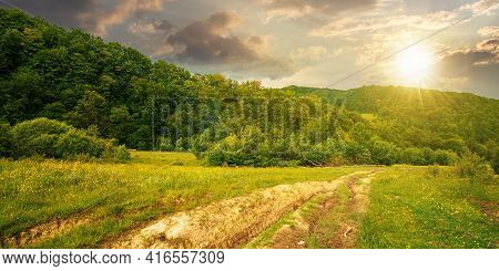 Dirt Road Through Forested Countryside At Sunset. Beautiful Summer Rural Landscape In Mountains. Adv