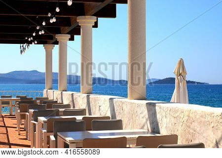 Beautiful Picturesque Summer Cafe With Columns By The Sea. Brown Tables Against The Backdrop Of The