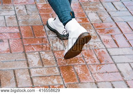 A Person Wears Big White Boots At The Wet Sidewalk Tiles Of The Street. Rain. Wet Weather. Bad. Stro