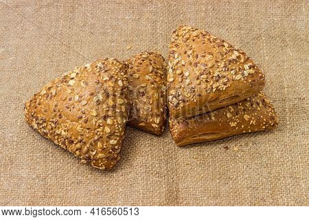 Triangular Breads Sprinkled With Different Seeds On A Sackcloth