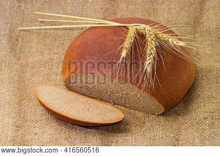 Partly Cut Round Loaf Of Hearth Brown Bread Made With Wheat And Rye Flour On A Sackcloth And Three W