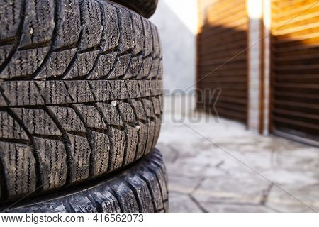Close-up Of Grooves On A Car Tire, Stones Stuck Inside The Rubber Selective Focus. . Winter Wheels A