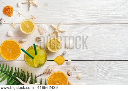 Summer Background With Fruit And A Cooling Drink. Oranges, Lemons, Juice And Shells On A White Backg