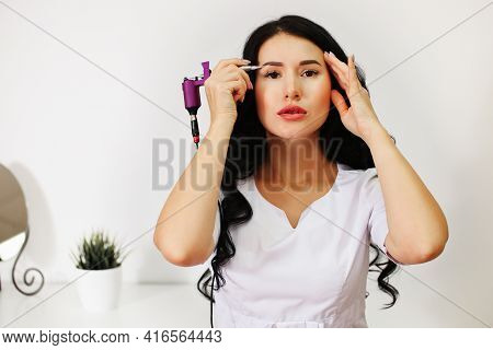 A Young Woman, A Master Of Permanent Make-up, Eyebrow, Eyelid And Lip Tufting, Tells The Patient How
