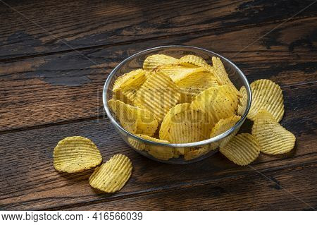 Ridged Potato Chips In Bowl On Wooden Background