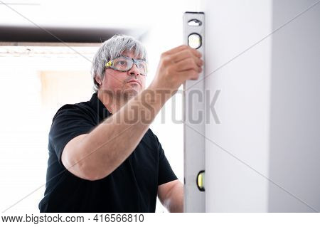 Construction Professional Checks The Wall With A Level During The House Renovation