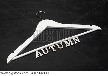 White Wooden Coat Hanger And Inscription Autumn On Black Background. Autumn Clothing Collection Conc