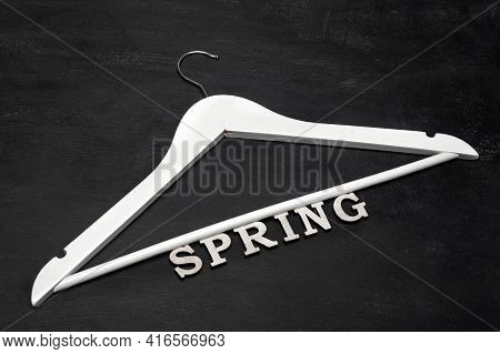 White Wooden Coat Hanger And Inscription Spring On Black Background. Spring Clothing Collection .