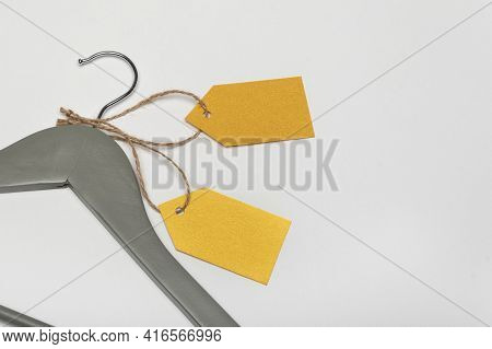 Grey Coat Hanger With Yellow Paper Labels. White Background. Blank Label , Mockup. Clothing Tag.