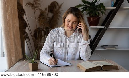 A Young Female Consultant Doctor Speaks On The Phone, Consults, Sits At A Wooden Table With Books An