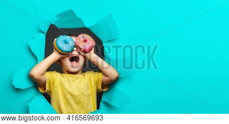 Happy cute boy is having fun played with donuts on black background wall. Bright photo of a child. Colored donuts