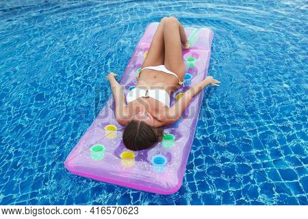 Enjoying suntan. Vacation concept. Top view of slim young woman in bikini on the pink air mattress in the swimming pool.