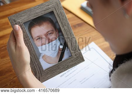 Woman Crying Over Portrait Of Deceased Young Man Closeup
