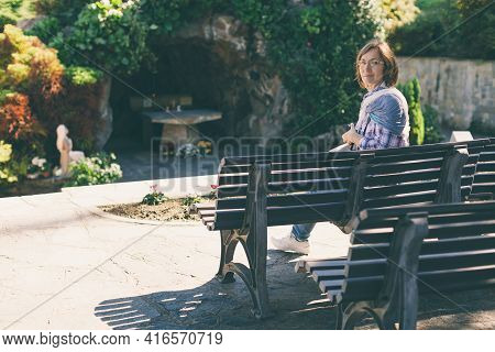 Pensive Middle Aged Woman Is Sitting Alone Outdoors On Bench. Senior Lady Relaxing In A Deserted Pla
