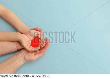 Hands Women Hold Drop Of Blood On Blue Background.concept Of Give Blood Donation, Blood Transfusion,