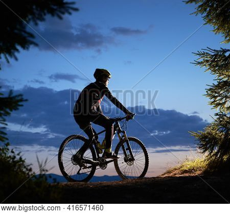 Side View Of Man Riding Bike Under Blue Evening Sky With Clouds. Silhouette Of Male Bicyclist Riding