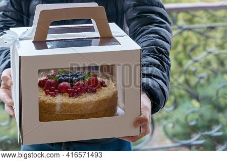 Human Hands Holding Cardboard Box With Holiday Cake Decorated With Berries. Spring Time, Person On T