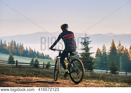 Back View Of Cyclist In Cycling Suit Riding Bike On The Trail With Coniferous Trees And Hills On Bac