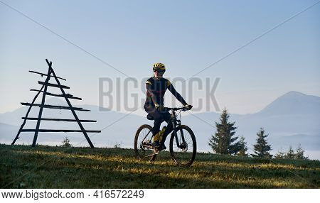 Silhouette Of Man In Cycling Suit Riding Bicycle On Grassy Hill. Male Bicyclist In Safety Helmet Enj
