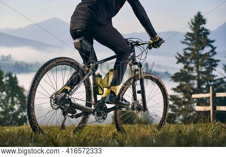Close Up View Of Man Cyclist In Cycling Suit Riding Bicycle On Grassy Hill. View Of Majestic Mountai