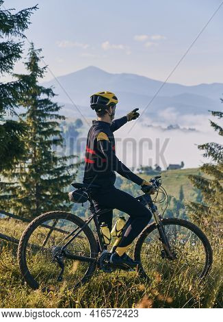 Back View Of Young Man In Cycling Suit Standing On Grassy Hill Near Bicycle And Pointing Finger At M