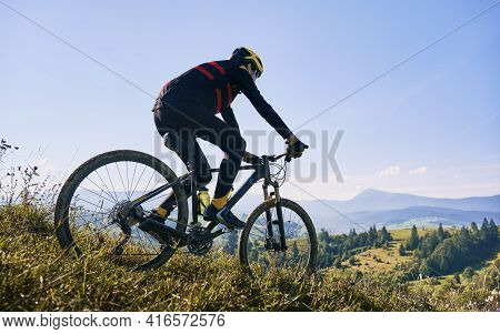 Horizontal Snapshot Of Man Riding His Bike In The Mountains In Early Foggy Morning Going Downhill. P