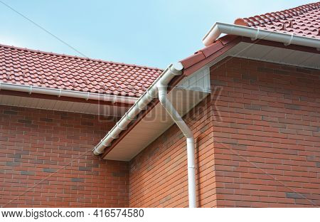 A Close-up On Plastic Rain Gutters, Downspout, Soffit And Fascia With A Box-end On The Corner Of A B