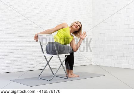 Yoga With A Chair. Adult Caucasian Woman Sits And Practice Side Twists With Props On A Mat In Loft W