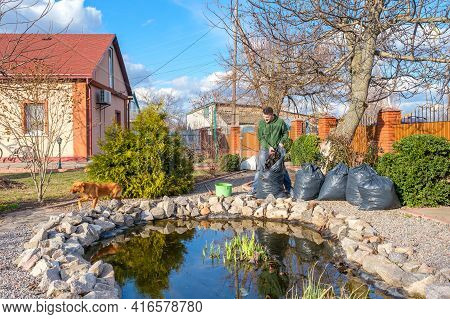 Mature Caucasian Man Cleans A Garden Pond From Water Plants, Falling Leaves And Places Them In A Tra
