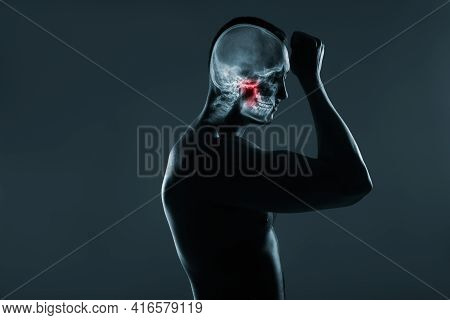 X-ray Of A Man's Head. Medical Examination Of Head Injuries. Jaw Joint Is Highlighted By Red Colour.