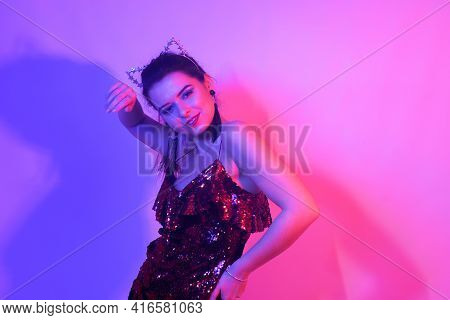 Gorgeous Girl Dancing In A Neon Light. A Girl In A Red Shiny Dress And With Cat Ears Is Dancing At A